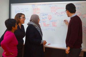 A group of 4 people standing beside a whiteboard. The person on the right is drawing something and the 3 on the left are looking at it