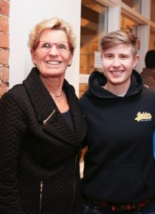 Kathleen Wynne and Stella Green pose for the camera, smiling. Both are wearing black and have short blonde hair. Kathleen is wearing red rimmed glasses.