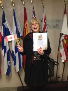 Dagmar Schroeder is smiling holding a certificate and a Canadian flag, standing in front of a bunch of different flags standing against a wall