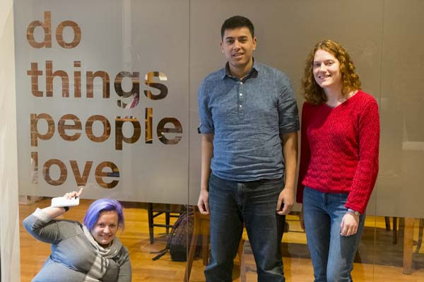 "3 People standing next to words on wall ""do things people love"""