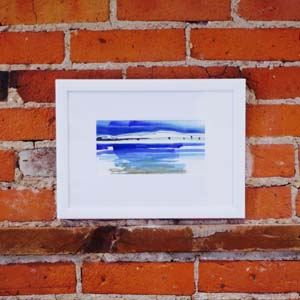 A photo of an artwork hung up on a red brick wall in a white frame.