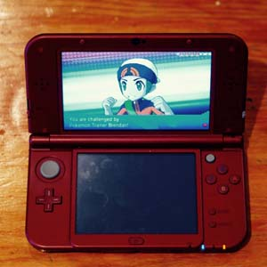 A photo of a Nintendo DS with a character on the screen