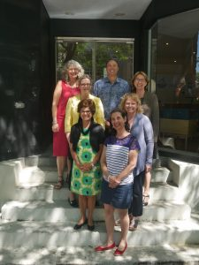 A group photo of 7 people standing on different levels of the stairs outside the Stella's Place building.