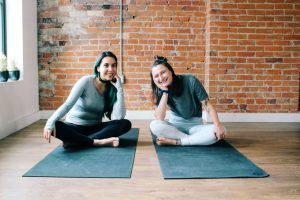 Two people sitting cross legged on black yoga mats smiling into the camera. Behind them is a red brick wall.
