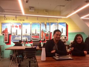 """A photo taken in a room with tables, two people are sitting at a table smiling at the camera. In the background on the wall is a mural that says """"Greetings from Toronto"""""""