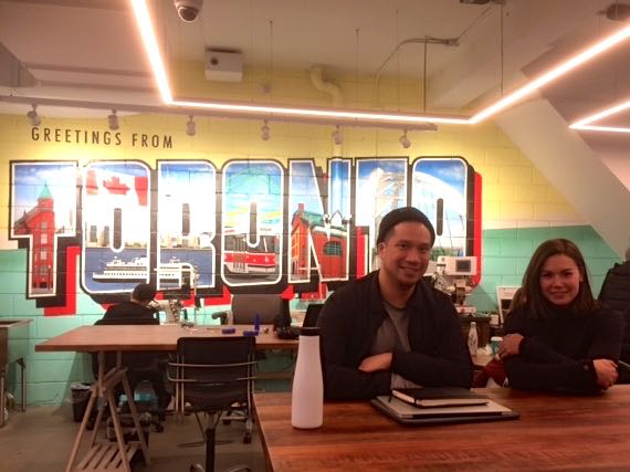 "A man and women sitting at a table in coffee shop with books and a waterbottle. Illustrated wall art of ""Greetings from Toronto"" in the background"
