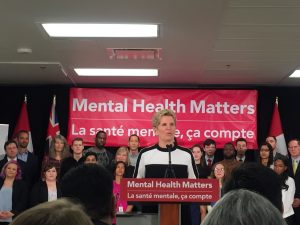 """Kathleen Wynn standing at a podium speaking into a microphone with a crowd of people around listening. In the background is a large red banner with white text """"Mental Health Matters"""""""
