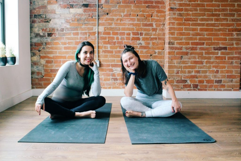 Two women smiling with their heads in their hands, sitting on yoga mats in empty room with brick wall in the background