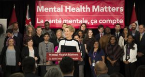 """Kathleen Wynn standing at a podium smiling with a crowd of people around listening. In the background is a large red banner with white text """"Mental Health Matters"""""""