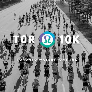 """A black and white aerial photo of people running for a marathon on a street with white text overlaid """"TOR 10K"""" in big bold letters with the lululemon logo and with smaller white letters underneath """"Toronto Waterfront 10K"""""""