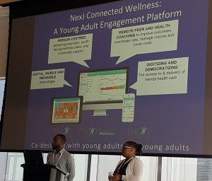 """Tendai & Funmi up on a stage presenting with a large projection screen behind them that reads """"NexJ Connected Wellness: A Young Adult Engagement Platform"""""""