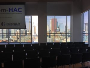 An empty room setup for an event with chairs in the foreground and big windows with a view of the Toronto city skyline.
