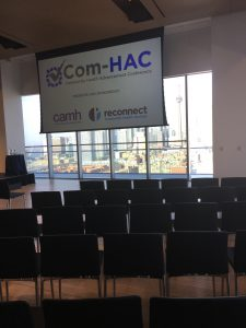 """An empty room setup for an event with chairs in the foreground and a large projector screen hung from the ceiling at the front that reads """"Com-HAC"""""""