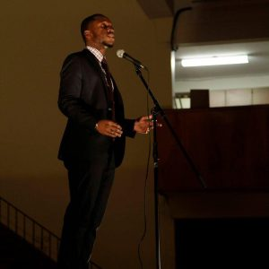 Funmi, dressed in a black suit, speaking into a microphone