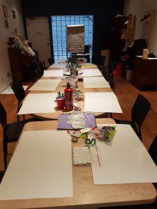 A photo of a n empty room, looking down two tables prepared with blank sheets of paper set out and groups of art supplies.