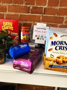 A pantry shelf of packaged food, there's peppers, morning crisp cereal, Lucky charms and coffee bags.