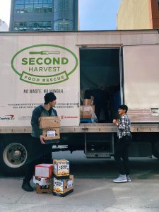 A photo of a Second Harvest Truck parked outside and 2 people talking to each other with one person holding a box with 4 other boxed at their feet.
