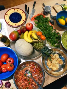 A top down photo of a table full of food. There's a fruit bowl with bananas and pineapple, a bowl with dip and chips, a platter of greens and a bowl of tomatoes.