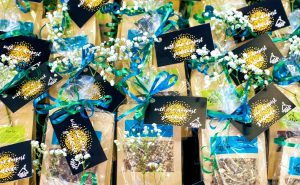 """A photo of a bunch of brown paper gift bags, wrapped in plastic with a bow, a stem of baby's breath flower and a note that says """"with our deepest gratitude"""""""