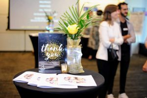 """A sign that says """"thank you"""" with gold glitter design. To the right of it is a vase of yellow flowers and a green leaf. In the background blurred out, you can see a crowd of people."""