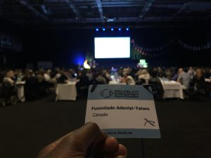 """A photo of a hand holding a name tag that reads """"Funmilade Adeniyl-Taiwo"""" """"Canada"""". The photo looks out at a blurred out conference room with a crowd of people."""