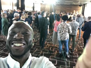 A selfie of Funmilade at the conference. Funmilade is smiling into the camera, with a crowd of people behind