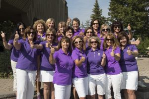 A group of people, all wearing a short sleeve purple polo shirt and white shorts. They are all smiling and holding out a thumbs up to the camera.