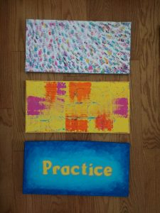 """3 rectangular canvases stacked on top of each other on a wooden surface. The top one is a bunch of small textured stokes in different colours. The middle is yellow canvas with brushstrokes of pink and orange. The bottom is a blue painted canvas with yellow text in the middle that reads """"Practice"""""""