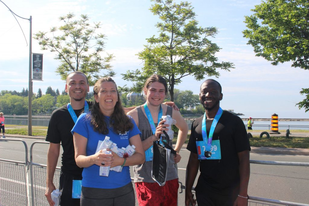 A group of four people smiling for the camera, holding water bottles and wearing blue lanyards after running a race.