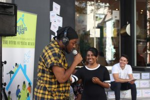 A photo of a person speaking into a microphone, wearing a yellow plaid t-shirt. Behind them are two people looking at them and smiling.