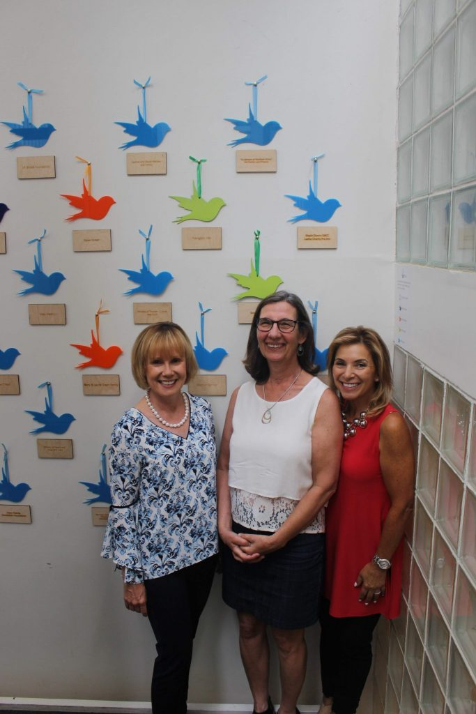 A group of three people standing in front of the donor wall at Stella's Place. A wall of different coloured illustrated birds on a white wall.