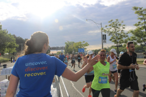 A person wearing a blue t-shirt on the left is reaching over a divider and high-fiving the runners as they run by in the crowd.