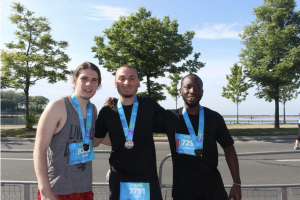 3 people standing together posing for the photo in embrace. All 3 are wearing workout clothes and wearing blue lanyards with a medal on them.