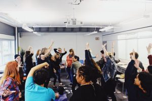 A photo of Stella's Place staff doing a group stretch with arms raised high in the air.