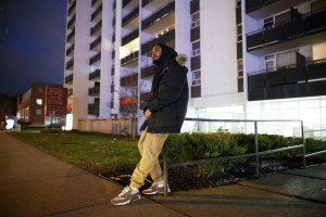 Jah-Reign sitting and leaning against a handrail. In the background is a condo building, lit up by lights in the night.