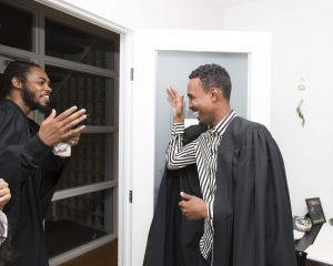 Two people about to shake hands, both are Healers, about to graduate from the Community Healing Project and are wearing black graduation gowns.
