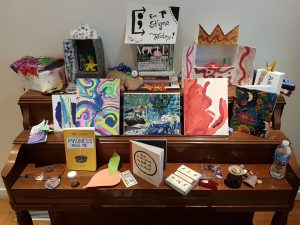 A wooden piano covered in different pieces of artwork including paintings, drawings, crafts and little crafts.