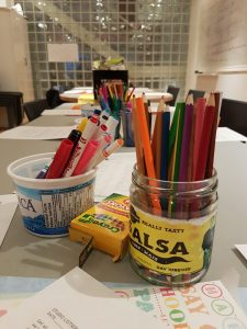 A photo of Stella's Studio supplies, there are a bunch of pencil crayons in an old empty sals jar in the foreground.