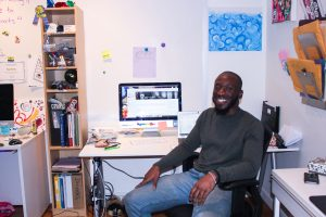 A portrait of staff member Funmi, who is sitting down at a desk with a computer, with lots of knick knacks, artwork and papers covering office walls.