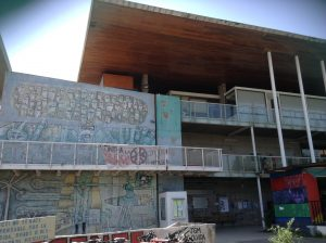A photo of a 3 level building with graffiti art on one wall.