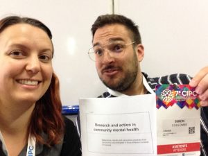 A selfie of Steph & Simon smiling and holding up papers.