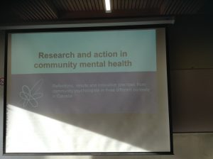 """A projector screen that reads """"Research and action in community mental health"""""""
