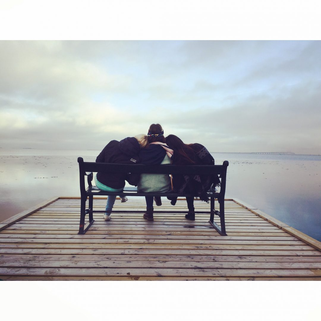 Three people leaning on each other, sitting on a bench on a pier overlooking a lake with pastel colours.