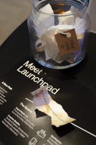 """A closeup photo of crumpled paper on top of a flat black poster that reads """"Meet Launchpad"""" in white text."""