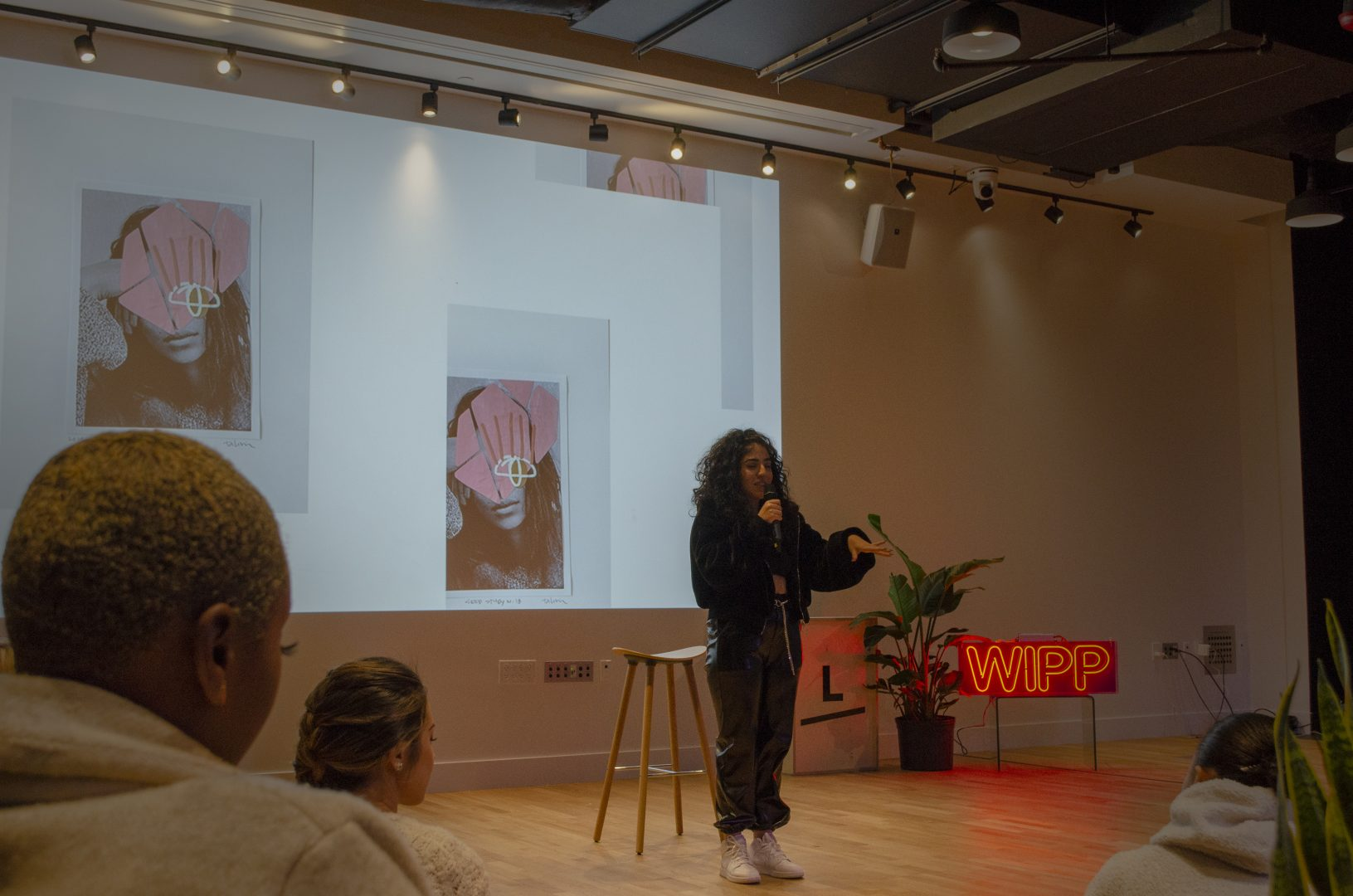 A person is standing at the front of the room with a microphone, mid speech. Behind them is a stool and projected onto the wall behind is some collage art work. The room is dark with the only light coming from the projection and a red neon light casting a red glow onto the floor.