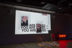 "WIPP event:Projected screen on wall with art that reads ""You are loved"" 3 times.  A pile of neon lights sit on the ground surrounded by darkness."