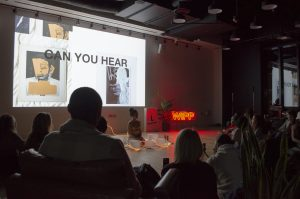 "WIPP Event: Presentation, person sitting at the front of the room, wrapped in lights. Screen in the background that says ""Can you head"" with artwork. Audience is in darkness."