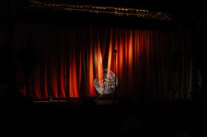 A photo of a red curtain on a stage with a light shining in the middle through the darkness