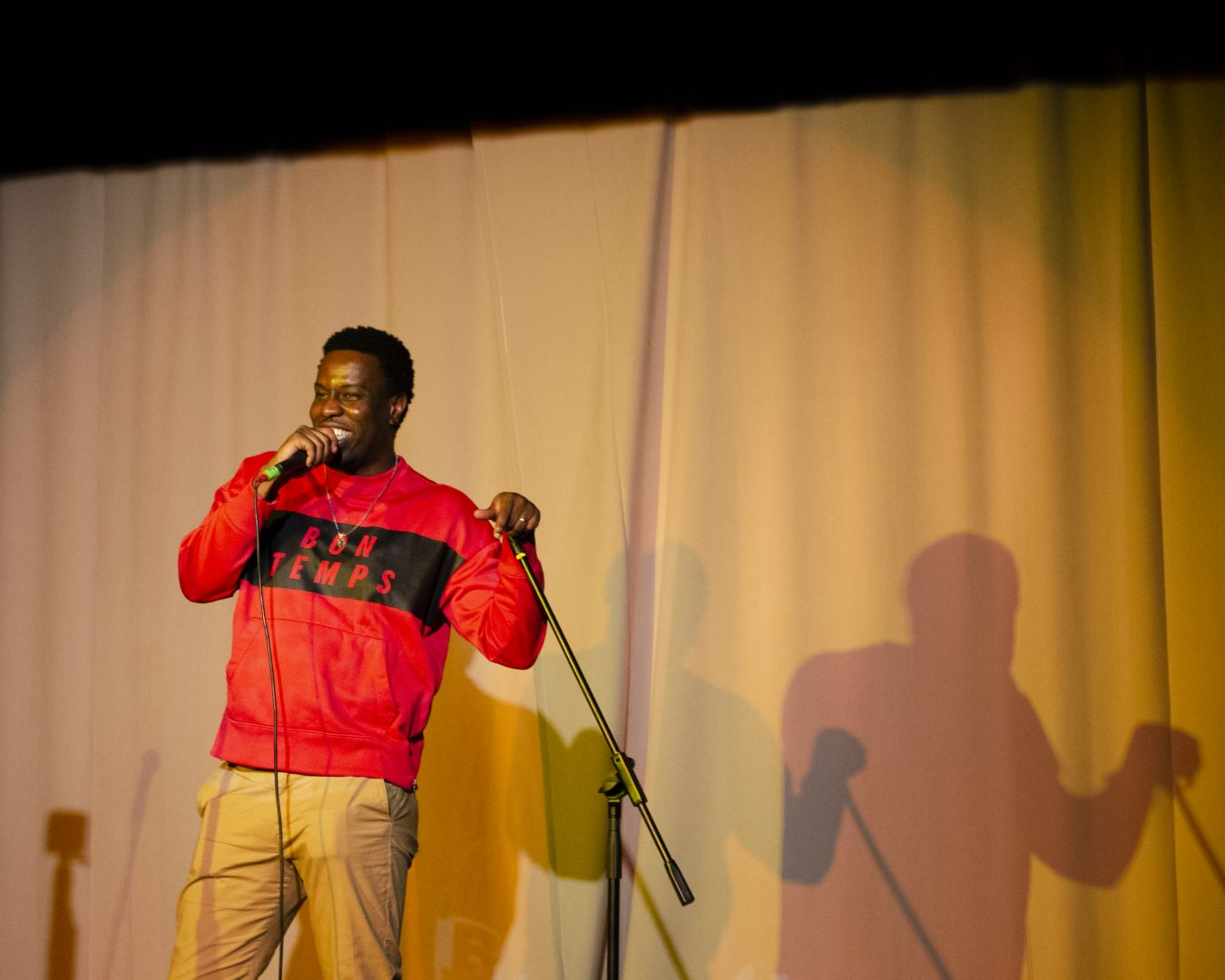 Asante, Stella's Place Peer Training Support Manager speaking into a microphone with a yellow curtain behind him.