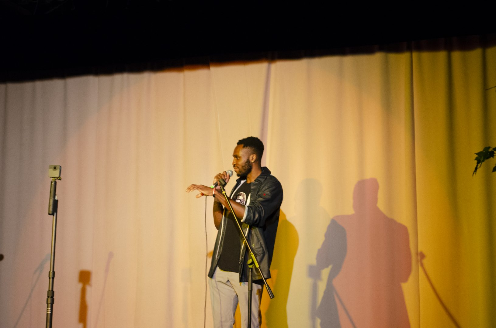 """Boyojoy giving an intro to his collaborative album """"Broken Record' standing on stage speaking into a microphone with a yellow curtain behind."""